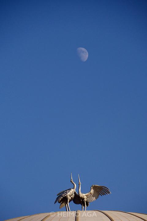 Uzbekistan, Tashkent. Crane sculpture on the roof of Congress Center, under the rising moon.