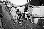 A woman cooks dinner a camp for those displaced by the recent earthquake in Petionville, outside Port-au-Prince, Haiti.