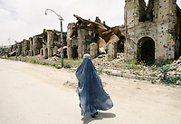 A woman in a burka, walking up what was the High Street of Kabul.The fight (1992 to 1995) between warlords Ahmad Shah Massoud of the Jamiat-e Islami and Gulbuddin Hekmatyar from the Hezb-e Islami, destroy one third of the Afghan capital.