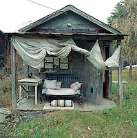 A dilapidated outbuilding has been converted into a guest cabin with a porch furnished with recycled flea market furniture