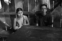 Couple at home with infant in jungle village on the Rio Napo in eastern Ecuador.