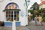 "Portmeirion, in North Wales, is a resort, where no one has ever lived. A self-taught Welsh architect named Sir Clough Williams-Ellis built it out of architectural salvage between the 1920s and 1970s, loosely based on his memories of trips to Portofino. Including a pagoda-shaped Chinoiserie gazebo, some Gothic obelisks, eucalyptus groves, a crenellated castle, a Mediterranean bell tower, a Jacobean town hall, and an Art Deco cylindrical watchtower. He kept improving Portmeirion until his death in 1978, age 94. It faces an estuary where at low tide one can walk across the sands and look out to sea. At high tide, the sea is lapping onto the shores. Every building in the village is either a shop, restaurant, hotel or self-catering accomodation. The village is booked out at high season, with numerous wedding receptions at the weekends. Very popular amongst the English and Welsh holidaymakers. Many who return to the same abode season after season. Hundreds of tourists visit every day, walking around the ornamental gardens, cobblestone paths, and shopping, eating ice-creams, or walking along the woodland and coastal paths, amongst a colourful assortment of hydrangea, rhododendrons, tree ferns and redwoods. The resort boasts two high class hotels, a la carte menus, a swimming pool, a lifesize concrete boat, topiary, pools and wishing wells. The creator describes the resort as ""a home for fallen buildings,"" and its ragged skyline and playful narrow passageways which were meant to provide ""more fun for more people."" It does just that.///Pocket Money Shop and two elderly women walking up the cobblestone path."