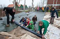 Grundschulklasse, Schulklasse legt einen Schulteich, Schul-Teich, Teich, Gartenteich, Garten-Teich im Schulgarten an, Teichfolie wird auf das Schutz-Flies, Schutz-Vlies ausgerollt, ausgelegt
