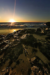 Sunset in Busselton beach, Australia with rocks on the shore with crashing waves