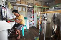 At the APDS association's premises, Suriadi, 29 years old, takes care of production. He checks the honey's quality and also monitors the dehydrating process that lowers the honey's moisture content from 27% to 21%, an indispensable step that prevents rapid fermentation and thus allows for the marketing of the honey. APDS produced 18 tons of honey in 2014 in the territory covered by six villages.///Dans les locaux de l'association APDS, Suriadi, 29 ans, s'assure de la production. Il contrôle la qualité du miel et suit également le processus de déshumidification qui permet d'abaisser son taux d'humidité du miel de 27% à 21%, une étape indispensable pour éviter une fermentation rapide et permettre ainsi sa commercialisation. APDS a produit 18 tonnes de miel en 2014 sur le territoire de six communes.