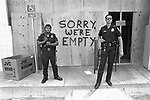Two armed officers stand guard out front of an electronics store on Sunset Blvd. and La Brea after being looted by rioters.