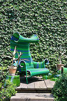 A green chair is set on a decked terrace area in a garden against the backdrop of an ivy covered wall. Agave plants grow in pots nearby.