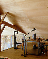 The mezzanine office space is furnished in reto style and nestles under part of the vast plywood-clad roof