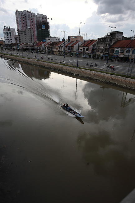 A small boat travels up the Saigon River in Ho Chi Minh City, Vietnam. Sept. 9, 2011.