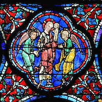 Jesus, flanked by 2 angels, collects the soul of Mary depicted as a naked child, to take her to heaven. The Elevation of the Soul, from the Glorification of the Virgin stained glass window, in the nave of Chartres Cathedral, Eure-et-Loir, France. This window depicts the end of the Virgin's life on earth, her dormition and assumption, as told in the apocryphal text the Golden Legend of 1260. Chartres cathedral was built 1194-1250 and is a fine example of Gothic architecture. Most of its windows date from 1205-40 although a few earlier 12th century examples are also intact. It was declared a UNESCO World Heritage Site in 1979. Picture by Manuel Cohen