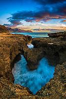 A heart-shaped rock formation along the coastline at sunset near Ka'ena Point, West O'ahu.