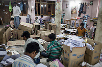 A worker (extreme right) fold the current issue of Khabar Lahariya weekly newspaper, after receiving the files from the newspaper's Chitrakoot office, in Allahabad, Uttar Pradesh, India on 06 December 2012. Photo by Suzanne Lee / Marie Claire France