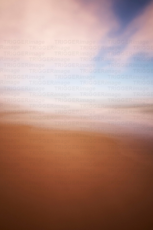 Blurry image of sky and sandy beach in summer