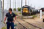A CSX conductor keeps a watchful eye on traffic at a road crossing as his train switches tank cars in a refinery in heavily industrialized Northwest Indiana.