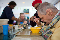 Caregiver Paul Marie Obas (red hat) helps Randy Russo, 60, eat in the residences in Malone Park at the Fernald Developmental Center in Waltham, Massachusetts, USA.  Ronnie and his twin Randy, both blind and unable to speak, have lived at the Fernald Center for 55 years.