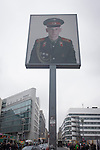 The portrait of a Soviet soldier sits high above modern Friedrishstrasse in modern Berlin at the location of  the former Checkpoint Charlie, the former border between Communist East and West Berlin during the Cold War. The Berlin Wall was a barrier constructed by the German Democratic Republic (GDR, East Germany) starting on 13 August 1961, that completely cut off (by land) West Berlin from surrounding East Germany and from East Berlin. The Eastern Bloc claimed that the wall was erected to protect its population from fascist elements conspiring to prevent the &quot;will of the people&quot; in building a socialist state in East Germany. In practice, the Wall served to prevent the massive emigration and defection that marked Germany and the communist Eastern Bloc during the post-World War II period.