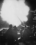 Accompanied by a thunderous roar and a blinding flash, Marine cannoneers launch a Long Tom projectile at Japanese positions in the Marianas. The Marines plug their ears and turn away from the weapon to shield themselves from the sound and brilliant light reflected by the smoke from the muzzle.