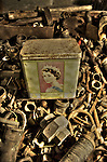 An old tin with a picture of Queen Elizabeth II in a box of old nuts and bolts