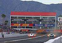 Feb 25, 2017; Chandler, AZ, USA; NHRA funny car driver Robert Hight (left) races alongside Alexis DeJoria during qualifying for the Arizona Nationals at Wild Horse Pass Motorsports Park. Mandatory Credit: Mark J. Rebilas-USA TODAY Sports