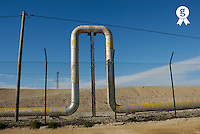 Bend in pipeline behind fence  (Licence this image exclusively with Getty: http://www.gettyimages.com/detail/200553554-001 )