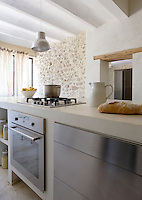A large kitchen island constructed from concrete has an integral hob and also houses an oven, dishwasher, cupboards and open shelves