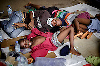 Eight members of the Fofana-Kamara family, who have become ill with ebola-like symptoms, lie on the ground waiting outside the Connaught Hospital in hope that they will soon be tested and receive treatment. Since there is no bed capacity at the moment, patients (who potentially pose a great risk) are forced to stay hours and days in a tent outside the hospital without any treatment. The floor of the tent is covered with body liquids which are potentially highly contaminated with ebola virus.