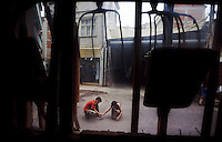 A window frames people on the street in a small, quiet, Turkish town where the local hardware store still sells wooden tools.