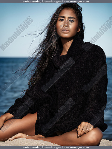 Beautiful young woman with long dark hair wearing a black sweater sitting on sand at the beach