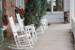 Porch with white rocking chairs and red geraniums at the Limpia Hotel, Ft. Davis, Texas.