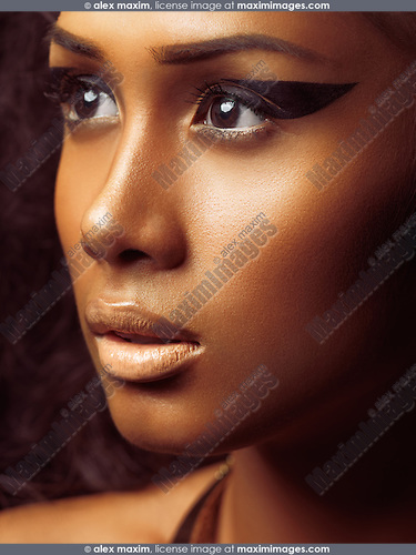 Exotic closeup beauty portrait of a young beautiful woman's face with golden skin and artistic makeup