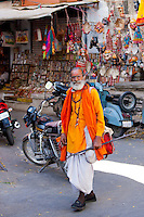Hindu sadhu holy man wearing traditional robes walks in old town in Udaipur, Rajasthan, Western India