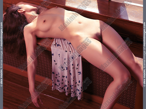 Sensual photo of a beautiful young woman lying naked on a window sill with sun light falling on her body
