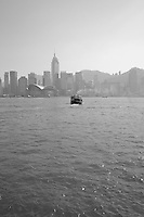 A classic view across the water of a Star Ferry heading towards the Hong Kong island skyline