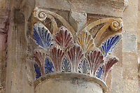 Carved and painted capital with palm leaf design in red, blue and yellow, at the junction of the nave and the transept in the Abbatiale Sainte-Foy de Conques or Abbey-church of Saint-Foy, Conques, Aveyron, Midi-Pyrenees, France, a Romanesque abbey church begun 1050 under abbot Odolric to house the remains of St Foy, a 4th century female martyr. The church is on the pilgrimage route to Santiago da Compostela, and is listed as a historic monument and a UNESCO World Heritage Site. Picture by Manuel Cohen