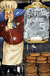 Delft, Holland. Fat baker model winking and with thumbs up to sell Gevulde Koeken cakes.