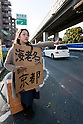 Mar. 16, 2011 - Tokyo, Japan - A woman hitch hikes on the side of the road following the recent earthquake and tsunami devastations which triggered dangerous nuclear explosions at the quake-hit nuclear power plant in Fukushima causing radiation levels to spike in Tokyo. Many people are fleeing Tokyo as the level of radiation is known to affect human health...(Photo by Christopher Jue/AFLO)