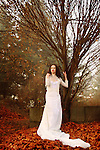 A brunette in a long white gown standing in a garden in front of a tree on a pile of fallen leaves.