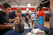 "First Lady Michelle Obama, Sam Kass, Senior Policy Advisor for Healthy Food Initiatives, and Top Chef head judge Tom Colicchio, center, watch as chefs from past seasons of Top Chef"" and students take part in a cooking competition at the Kleberg Rylie Recreation Center in Dallas, Texas, February 10, 2012. The event, which helped celebrate the second anniversary of the ""Let's Move!"" initiative, highlighted the work being done in schools across America to provide healthier food to students. .Mandatory Credit: Sonya N. Hebert - White House via CNP"