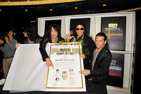 KISS - Tommy Thayer, Paul Stanley, Gene Simmons and Eric Singer .attending the 'KISS Monster' book launch, The Arts Club, London, England. .3rd July 2012.half length black suit jacket sunglasses shades  white print scarf band group leopard large giant oversized book hand finger pointing devil hand sign gesture .CAP/MAR.© Martin Harris/Capital Pictures.