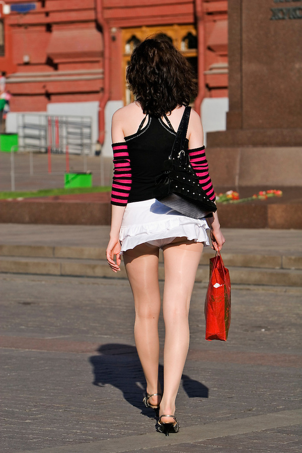 Moscow, Russia, 20/05/2007..A breeze catches the miniskirt of a girl walking on Red Square by the Kremlin during a heatwave.