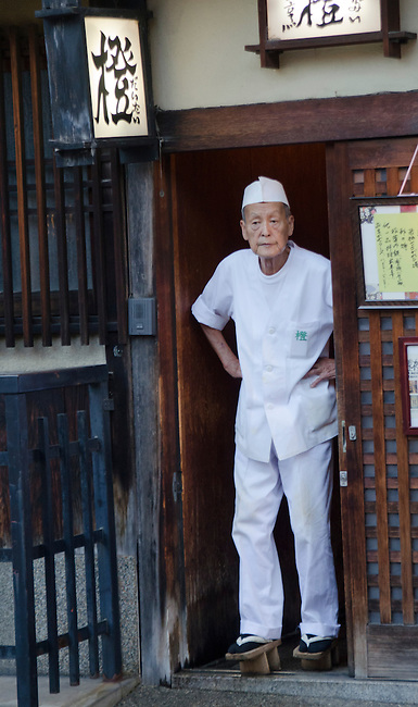 Japanese chef stands in the doorway of his Gion restaurant before opening in the evening