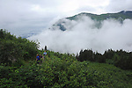 low lying clouds fill valley below the hikers who are walking up Mt Robert in Juneau, Alaska