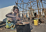 Louise Justine cooks for her family in a camp in rebel-held territory in the eastern Congo. Families displaced by fighting between rebel Tutsi General Laurent Nkunda and the Congolese military took refuge in this camp they established in the shadow of a United Nations base in the village of Kiwanja. According to aid workers and human rights groups, rebel soldiers executed some 150 people here in a 24-hour period in early November. The killings took place half a mile from the UN base, yet the 120 UN peacekeepers, part of the largest UN peacekeeping contingent in the world, did not take any action to stop the violence. ..