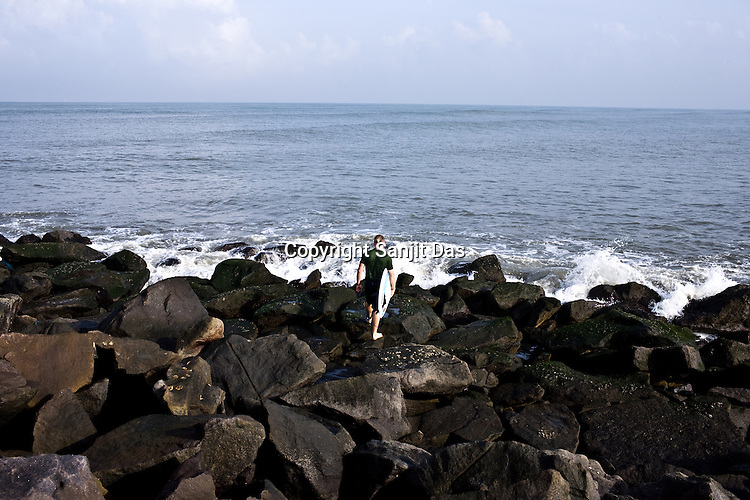 """Gaura Gopal, one of the Krishna devotees from the Kaliya Mardana Krishna Ashram is seen on the rock jetty of the Arabian Sea on the beach front of Mangalore, Karnataka, India.  ..Krishna devotees in the Gaudiya Vaishnava tradition of Hinduism, they are known collectively as the """"surfing swamis."""" The """"surfing ashram"""" is growing in popularity and surfing here is a form of meditation, a spiritual practice leading to heightened states of awareness."""