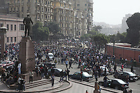 People watch protests near Tahrir Square while President Hosni Mubarak's National Democratic Party headquarters a day after it was set ablaze by protesters.