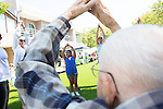 98 year old Bob Rynders arches his hands above his head as 8 year old Jessica Rodrigez does the same during a free exercise class during the Los Altos Stride and Ride event July 27.