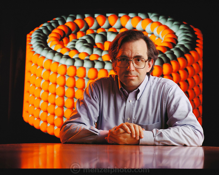 Nano / Micro Technology: Eric Drexler. Portrait of US nanotechnologist and author Eric Drexler. He is seated in front of a computer simulation of a diamondoid molecular bearing model of a robot he designed. This nanotechnology robot is so tiny it is made up of a precise number of atoms (orange and grey spheres). Although still on the frontiers of science, a robot like this may one day assemble molecules one-by-one, eat up pollutants, function as computers the size of a virus, or patrol the human body in search of cancer tumors. Eric Drexler developed the concept of nanotechnology in his books The Engines of Creation and Nanosystems. Model Released [1996]