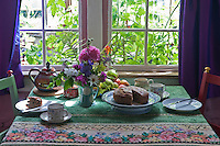 The tea table is laid with a delicious cake next to an arrangement of flowers fresh from the garden