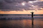 The sun sets on Kuta beach, Bali, Indonesia.