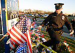 Seattle Police officer Jeff Mitchell steps over flowers, balloons and wreaths at a makeshift memorial to four slain police officers at the Forza Coffee Shop  in Lakewood, Washington, USA, on 2 December  2009. Four Lakewood officers were gunned down during a morning meeting at a local coffee shop on 29 November 2009.  Jim Bryant Photo. ©2010. ALL RIGHTS RESERVED.